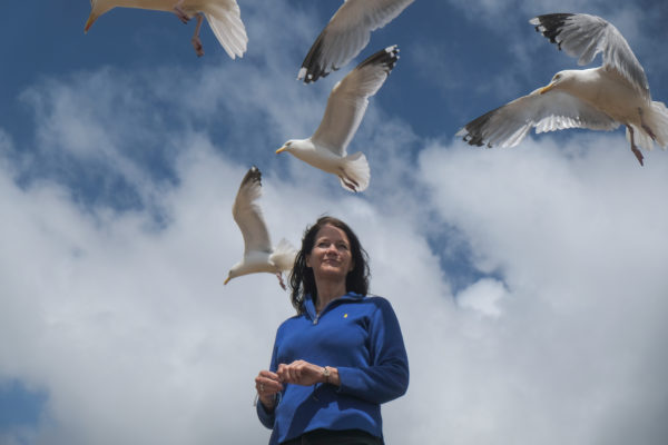 Lee Baker standing with seagulls above her head